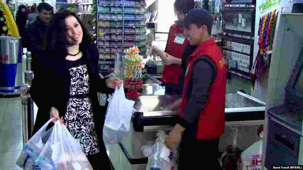 Komilzoda carrying grocery bags at a supermarket in Dushanbe