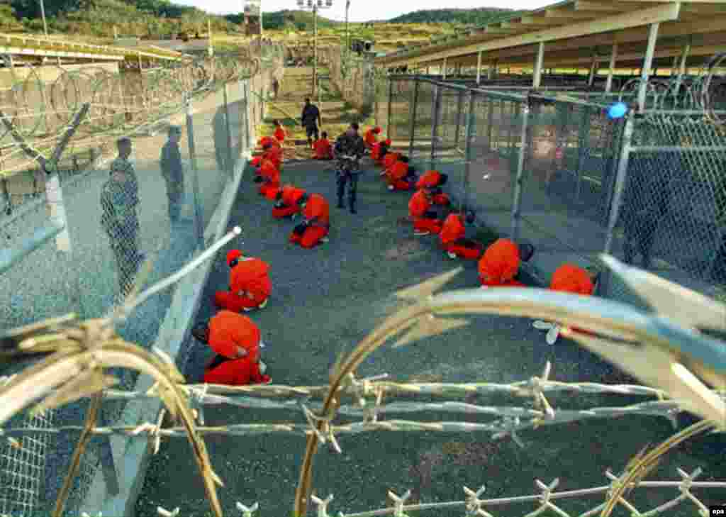 Guantanamo Bay detention center - Detainees in orange jumpsuits sit in a holding area under the eye of U.S. military police at Guantanamo Bay detention center (Camp X-Ray), released on January 18, 2002.