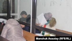 The defendants in the murder case of figure skater Denis Ten confer at the preliminary hearing in Almaty on December 25.