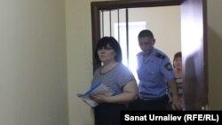 Бывший директор областного камерного оркестра Гульжан Алиева выходит из зала суда в сопровождении конвоя. Уральск, 1 июля 2016 года.
