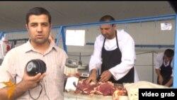 Журналист Радио Озоди Муъмин Ахмади демонстрирует видео-камеру в мясной лавке