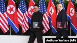 Лидер Северной Кореи Ким Чен Ын и Президент США Дональда Трамп держат в руках только что подписанные документы. Сингапур, 12 июня 2018 г.