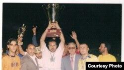 المدرب زياد داود سلمان وفي يديه كأس الكؤوس التي فاز بها لاعبو نادي الحسين الرياضي الأردني عام 2004
