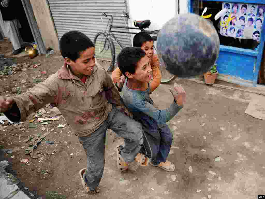 Afghan boys scuffle as they play football in a street in Kabul on July 28. Photo by Yuri Cortez for AFP