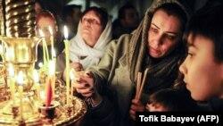 Besimtarët ortodoksë ndezin qirinjtë në një kishë në Baku të Azerbajxhanit. 7 dhjetor, 2019.
