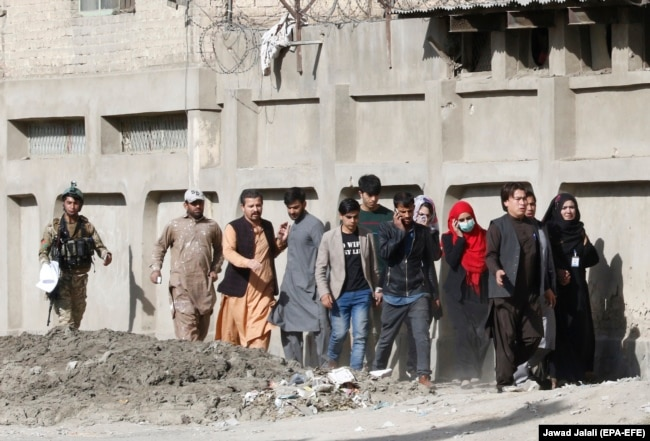 An Afghan soldier escorts rescued TV journalists after militants attacked the Shamshad TV station in Kabul in November.