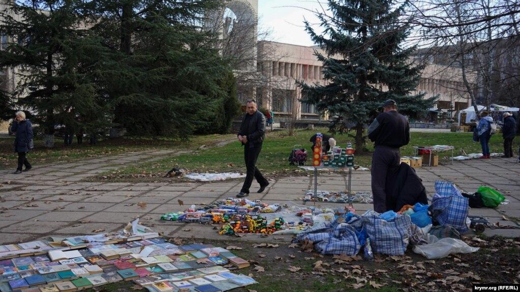 Книжно-игрушечный ассортимент вдоль тротуара в сквере на улице Киевской. Тут распродают свои домашние библиотеки и те, кто готовится переехать на материк