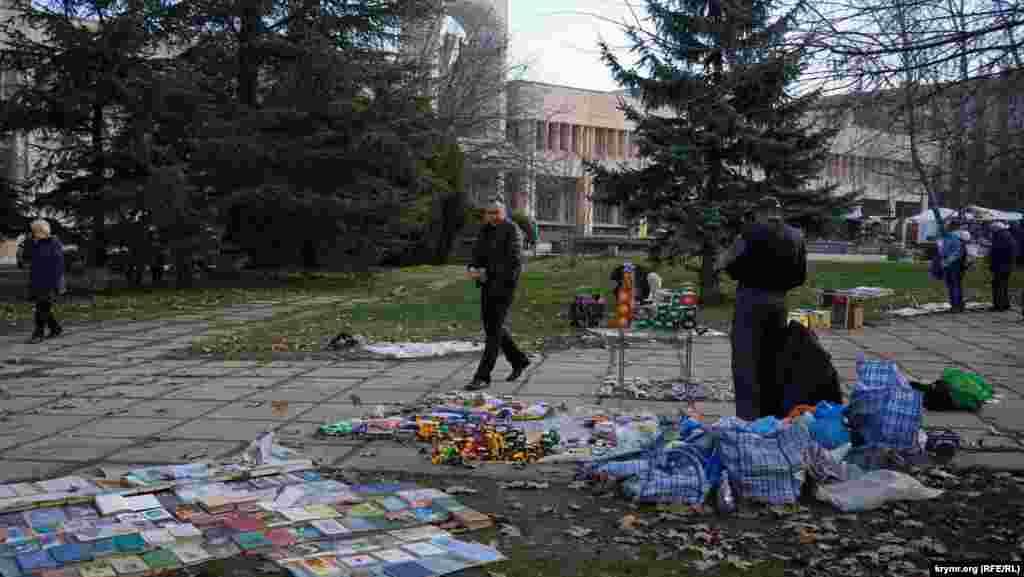 Книжково-іграшковий асортимент вздовж тротуару в сквері на вулиці Київській. Тут розпродають свої домашні бібліотеки й ті, хто готується переїхати на материк