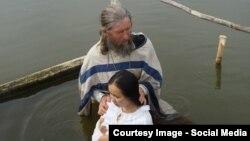Проповедник Игнатий Лапкин крестит прихожанку православной общины в деревне Потеряевка
