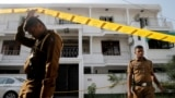 Police keep watch outside the family home of a bomber suspect, Sri Lanka