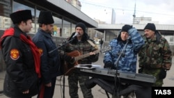 Cossack militia members (left) check out street musicians at the entrance to a Moscow subway station on November 14.