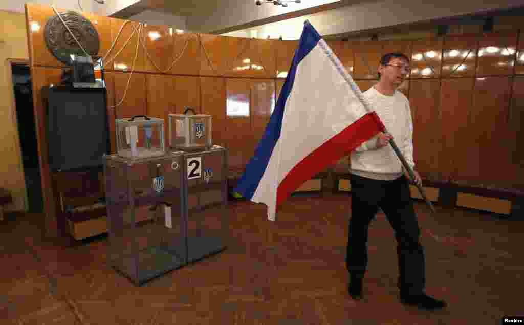 """Подготовка к назначенному на 16 марта """"референдуму"""" в Алупке: член избирательной комиссии несет крымский флаг. 12 марта 2014 года."""