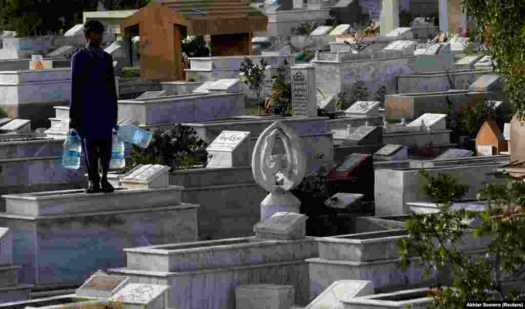 A boy with water for sale stands on a grave while waiting for customers in a cemetery in Karachi, Pakistan. (Reuters/Akhtar Soomro)