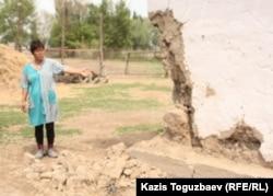 Жительница села Казатком Гульбаршин Иманбаева показывает угол дома, обвалившийся в результате землетрясения. Алматинская область, 6 мая 2011 года.