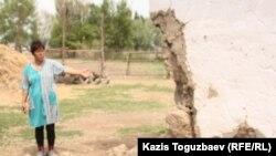 Житель села Казатком Гульбаршин Иманбаева показывает угол дома, обвалившийся в результате землетрясения. Алматинская область, 6 мая 2011 года.