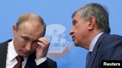 Russia -- Russian President Vladimir Putin (L) confers with his close ally Rosneft CEO Igor Sechin.