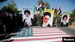 Iraqi Shi'ite Muslims from Hashed Shaabi hold portraits of Iran's late leader Ayatollah Ruhollah Khomeini (C), Supreme Leader Ayatollah Ali Khamenei (L) and Iraq's top Shi'ite cleric Grand Ayatollah Ali al-Sistani during a parade marking the annua