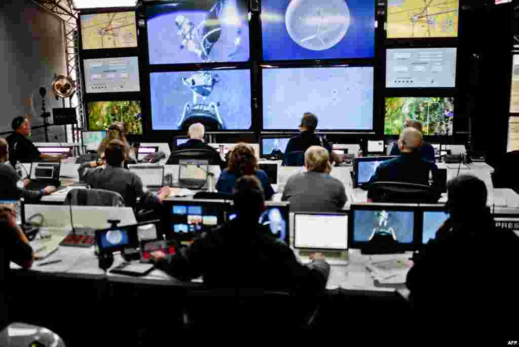 Crew members at mission control watch at the moment that Baumgartner steps off the capsule.