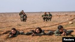 Female fighters of the Kurdish People's Protection Units (YPG) participate in military training in the western countryside of Ras al-Ain, Syria, in January.