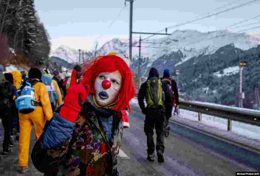 A man dressed as a clown is one of hundreds of climate protesters at the Davos economic conference in Switzerland. (AP/Michael Probst)