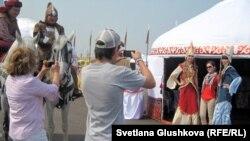 Туристы фотографируют девушек в казахских национальных одеждах у юрты. Иллюстративное фото.