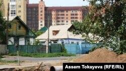 Частные дома на фоне нового многоэтажного жилого комплекса в Астане. Иллюстративное фото.