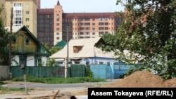 Частные дома на фоне нового многоэтажного дома в Астане.