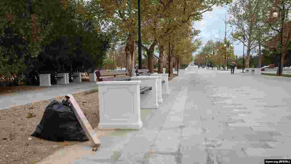 Мешок со строительным мусором возле скамейки на главной аллее парка