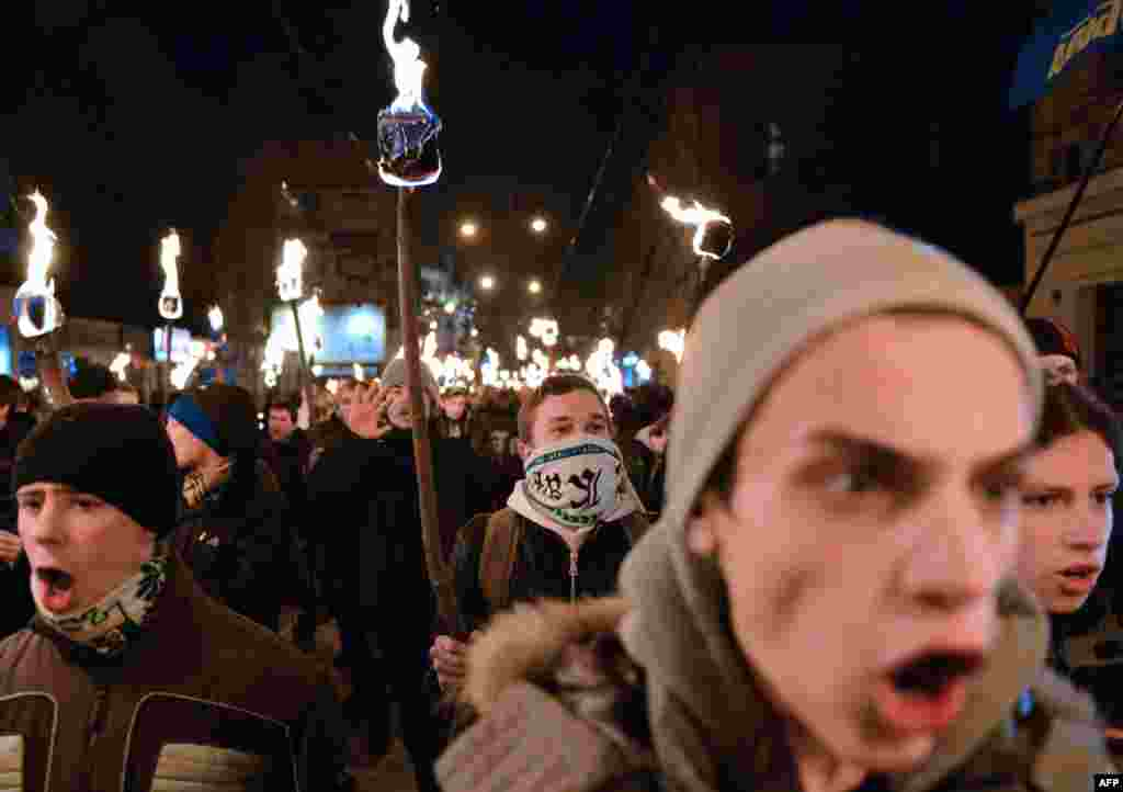 Nationalists hold torches during a march in the western Ukrainian city of Lviv on January 1, as they mark the 104th anniversary of the birth of Stepan Bandera, one of the leaders of the Ukrainian national movement. Bandera was responsible for a series of terrorist acts against Polish and Ukrainian civilians committed in interwar Poland. (AFP/Yuriy Dyachyshyn)