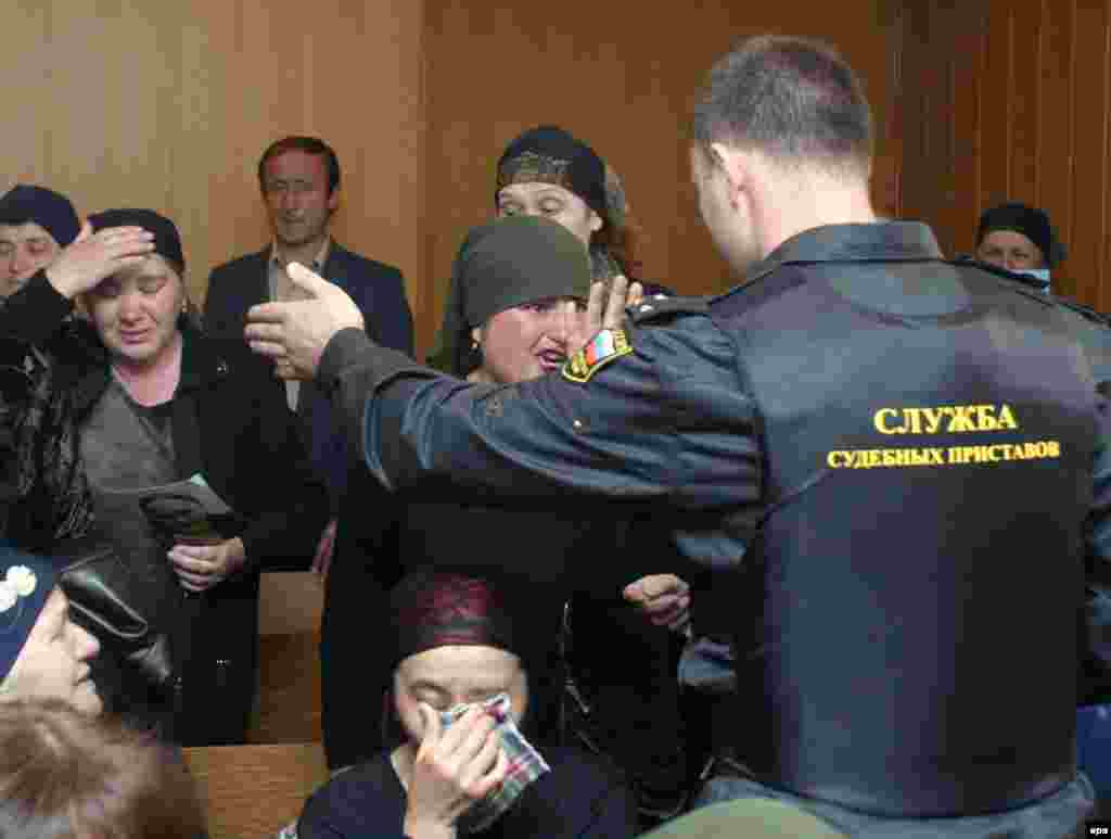 A bailiff tries to silence women speaking out during the trial of Nurpashi Kulayev, the only militant arrested during the Beslan hostage crisis, at a court in Vladikavkaz on May 19, 2005.