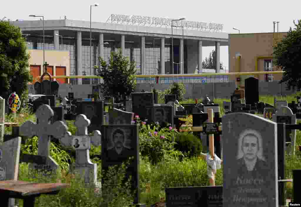 The terminal of Donetsk international airport is seen behind a cemetery.