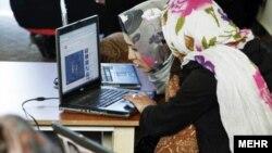 Две жительницы Ирана читают материалы в Интернете, архивное фото