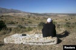 Мужчина-друз сидит на старом матрасе у границы Израиля и Сирии, наблюдая в бинокль за боевым столкновением на сирийской стороне