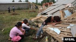 Женщина с детьми плачет на руинах своего разрушенного по указанию суда дома в поселке Бакай на окраине Алматы. 7 июля 2006 года.
