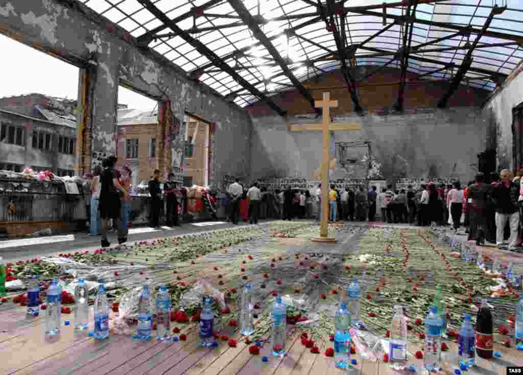 A memorial service in the ruined gymnasium of Beslan School No. 1 on September 1, 2006 (TASS) - Together with survivors, a number of independent investigators and journalists have denounced what they say was a botched-up rescue operation. Yury Savelyev, an explosives expert and State Duma deputy, published a report confirming the battle was triggered by soldiers firing grenades from a building across from the school.