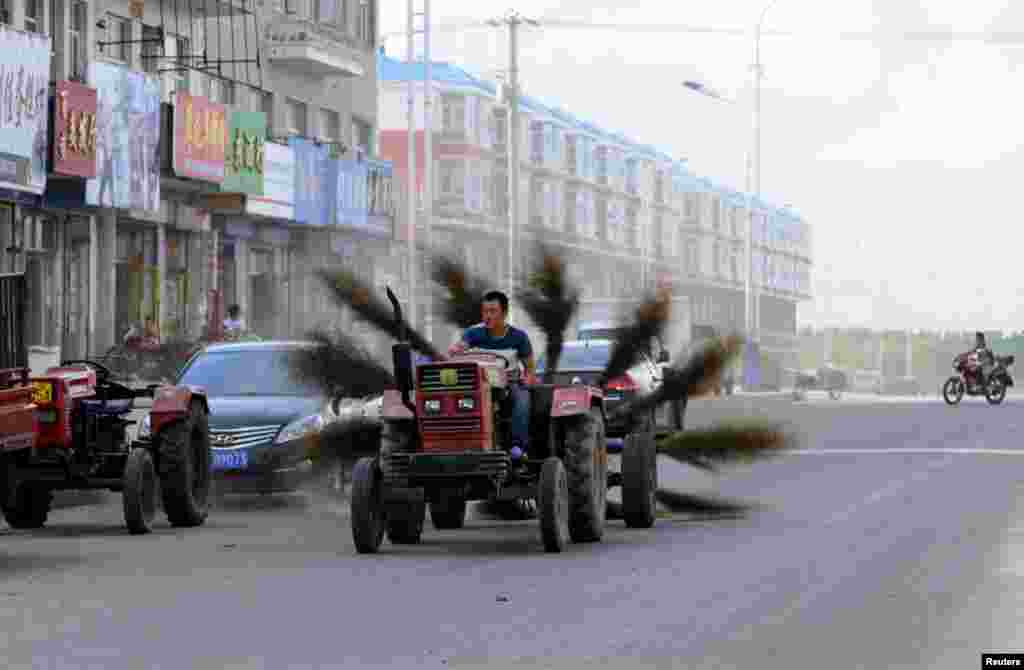 A man drives an improvised tractor with 12 brooms tied to the back, as he tries to clean a road in Mohe in China's Heilongjiang Province. (Reuters)