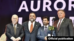 Armenia -- The co-founders of Aurora Prize for Awakening Humanity, Vartan Gregorian (L), Ruben Vardanyan (second from left) and Noubar Afeyan (R), pose for a photograph with its latest winner, Mirza Dinnayi, Yerevan, October 19, 2019.