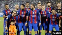 Lionel Messi (L) and Barcelona's team pose for photographs with six-year-old Afghan boy Murtaza Ahmadi