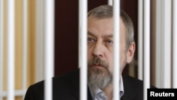 Former opposition presidential candidate Andrey Sannikau sits in a cage during a court hearing in Minsk in April.