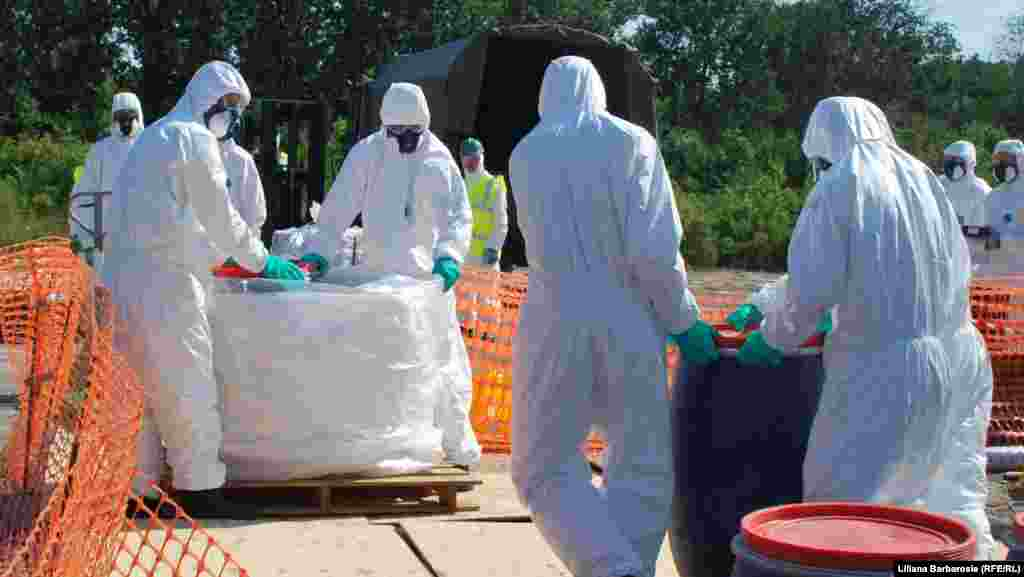 Chemical specialists collect and package dangerous pesticides in the village of Dceni.