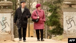 Пожилая пара входит во двор дворцового комплекса в Павловске через ворота, разрисованные нацистской свастикой. Санкт-Петербург, Россия. Иллюстративное фото.