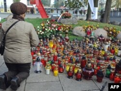 Верующая молится у могилы Ежи Попелушко в Варшаве