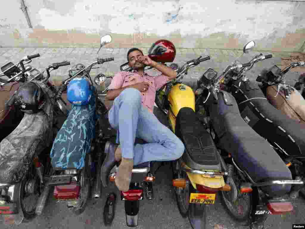 A man takes a nap on a motorbike outside a post office in Karachi.Photo by Athar Hussain for Reuters