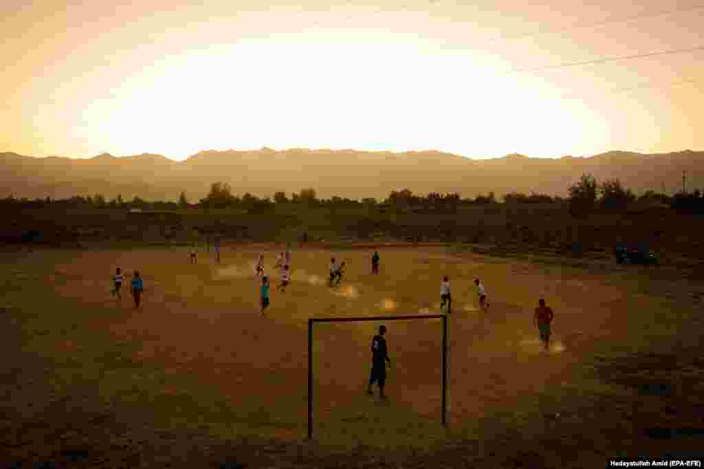 Afghan children play soccer in a field near a village on the outskirts of Kabul. (epa-EFE/Hedayatullah Amid)