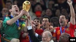 Испаниялық қақпашы Икер Касильяс ФИФА басшысы З.Блаттерден Әлем кубогын алып тұр. Йоханесбург, 11 шілде 2010 ж.