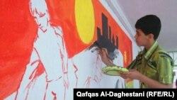 شاب يرسم لوحة على جدار مدرسته