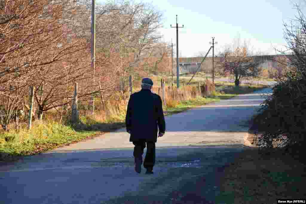 Літній чоловік кудись прямує сільською дорогою