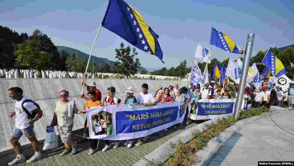 "Participants in the ""March for Peace"" carry the Bosnian national flag as they arrive at the Memorial Center in Potocari on July 10."