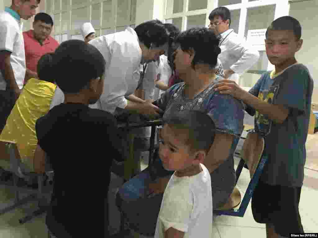Медицинские работники обследуют состояние здоровья граждан, находящихся в эвакуационном пункте.