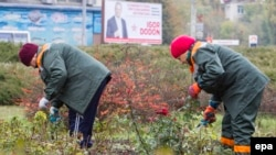Two Moldovan women work against the backdrop of an electoral campaign poster for presidential front-runner Igor Dodon in Chisinau on October 27.